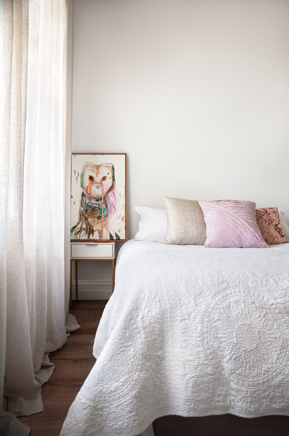 White bed with pink cushions and a painting on bedside table