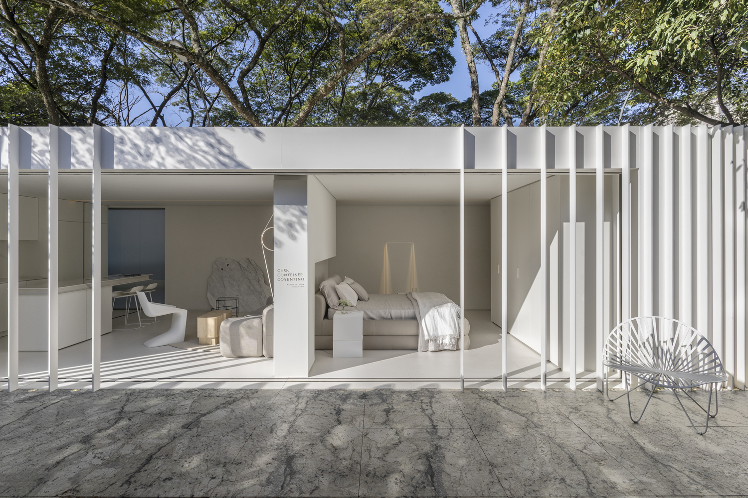 white shipping container house with bedroom and kitchen