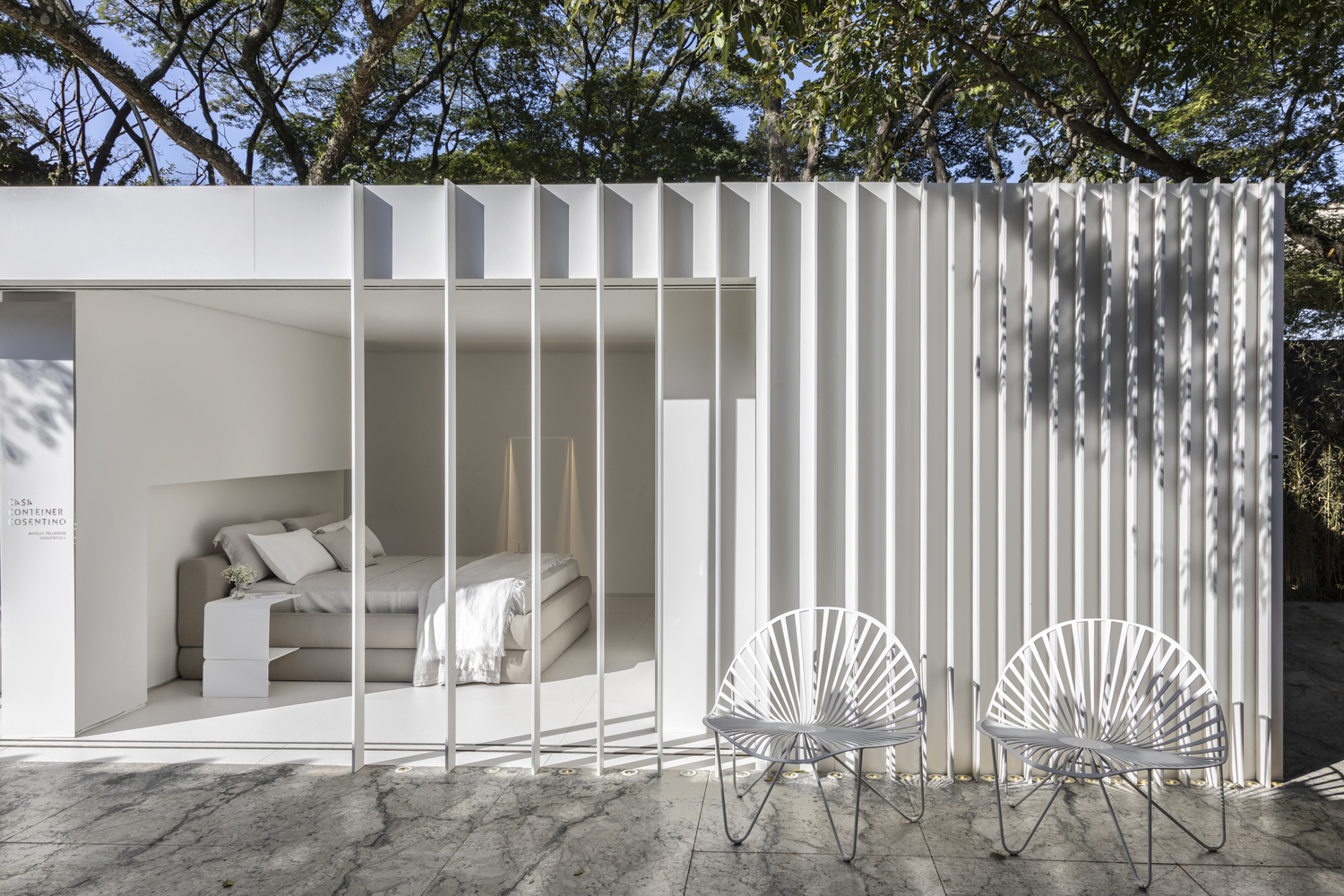 white shipping container house with beige bed